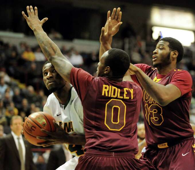 Siena's Imoh Silas (34), left, looks to the hoop as Iona's Taaj Ridley (0), center, and David Laury