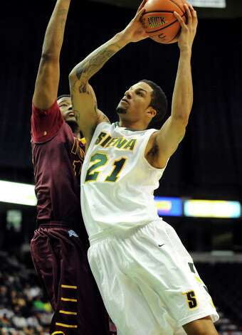 Siena's David Martens (21), right, shoots for the hoop as Iona's David Laury (13) defends during their basketball game on Friday, Jan. 4, 2013, at Times Union Center in Albany, N.Y. (Cindy Schultz / Times Union) Photo: Cindy Schultz / 00020599B