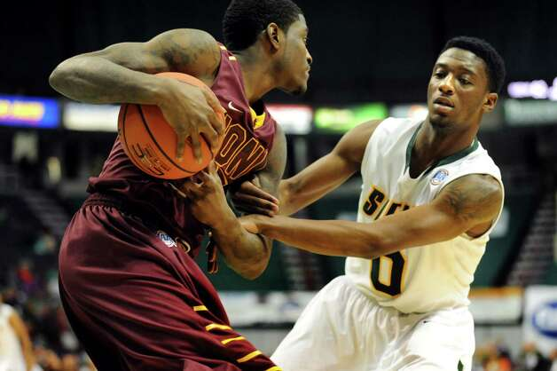 Siena's Rich Audu (0), right, fouls on Iona's A.J. English (5) during their basketball game on Friday, Jan. 4, 2013, at Times Union Center in Albany, N.Y. (Cindy Schultz / Times Union) Photo: Cindy Schultz / 00020599B