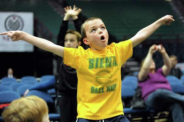 Siena ball boy Jeffrey Maddalone, 8, of Clifton Park dances to the music during a break in the action during their basketball game against Iona on Friday, Jan. 4, 2013, at Times Union Center in Albany, N.Y. (Cindy Schultz / Times Union) Photo: Cindy Schultz / 00020599B