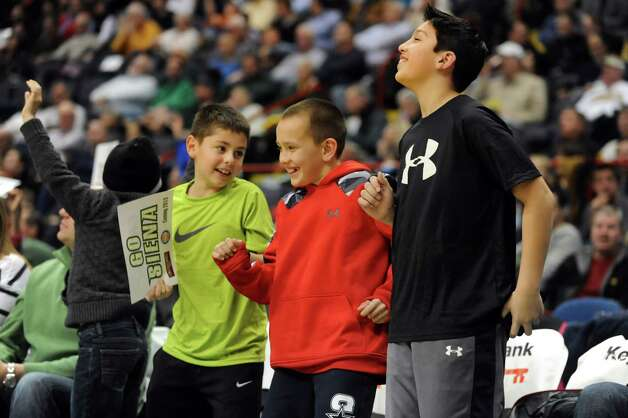 Siena fans Anthony Moffre, 11, left, Chris Ardito, 11, center, and Billy Lia, 10, all of Guilderland, try to get their image on the jumbotron during a break in the basketball action against Iona on Friday, Jan. 4, 2013, at Times Union Center in Albany, N.Y. (Cindy Schultz / Times Union) Photo: Cindy Schultz / 00020599B