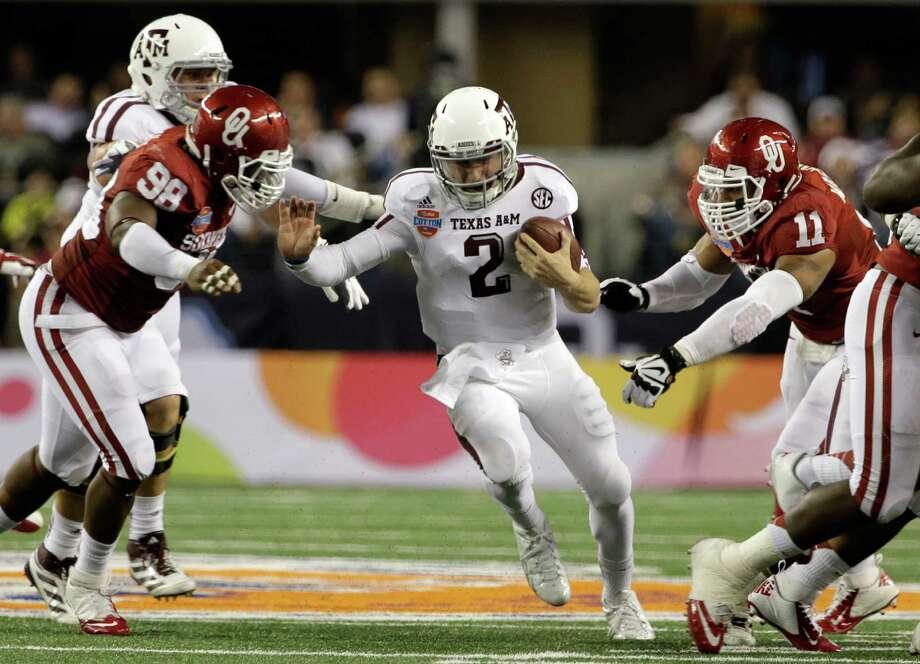 Texas A&M quarterback Johnny Manziel (2) runs between Oklahoma's Chuka Ndulue (98) and R.J. Washington during the second half of the Cotton Bowl NCAA college football game Friday, Jan. 4, 2013, in Arlington, Texas. (AP Photo/Tony Gutierrez) Photo: Tony Gutierrez