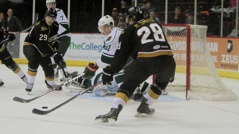 The Aeros' Tyler Cuma, center, tries to get in the way of a pass by the Stars' Reilly Smith during the Aeros' loss to their divisional and in-state rivals at Toyota Center on Friday. Smith assisted on the Stars' second-period, power-play goal.