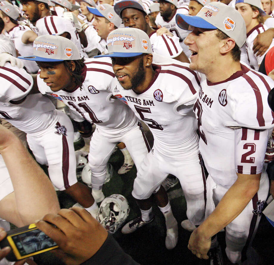 Texas A&M Aggies' Johnny Manziel (right) celebrates after the 77th AT&T Cotton Bowl Classic against the Oklahoma Sooners held Friday Jan. 4, 2013 at Cowboys Stadium in Arlington, Tx. The Aggies won 41-13. Photo: Edward A. Ornelas, Express-News / © 2012 San Antonio Express-News