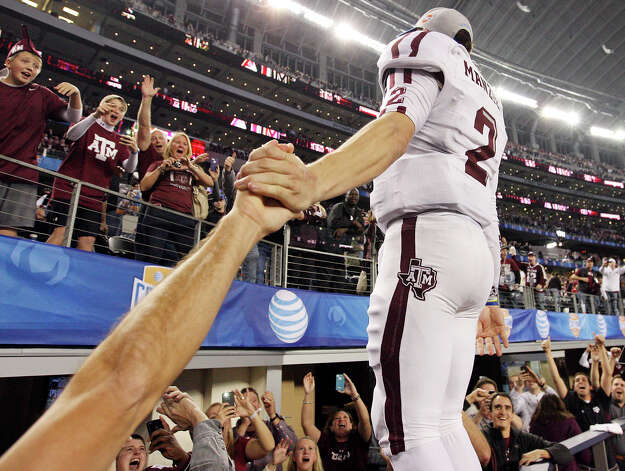 Texas A&M Aggies' Johnny Manziel celebrates with fans after the 77th AT&T Cotton Bowl Classic against the Oklahoma Sooners held Friday Jan. 4, 2013 at Cowboys Stadium in Arlington, Tx. The Aggies won 41-13. Photo: Edward A. Ornelas, Express-News / © 2012 San Antonio Express-News