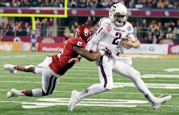 Texas A&M Aggies' Johnny Manziel tries to shake the tackle of Oklahoma Sooners' Demontre Hurst during second half action of the 77th AT&T Cotton Bowl Classic held Friday Jan. 4, 2013 at Cowboys Stadium in Arlington, Tx. A penalty was called on the play. Photo: Edward A. Ornelas, Express-News / © 2012 San Antonio Express-News