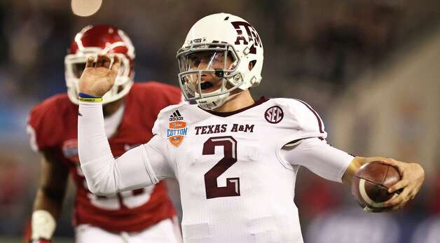 Texas A&M quarterback Johnny Manziel (2) scrambles from Oklahoma defensive back Javon Harris (30) for a first down during the first quarter of the Cotton Bowl college football game, Friday, Jan. 4, 2013, in Cowboys Stadium in Arlington. Photo: Nick De La Torre, Houston Chronicle / © 2013  Houston Chronicle