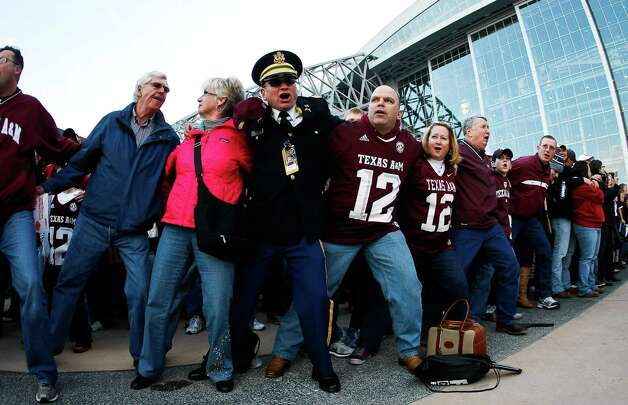 Captain Travis Almany, center, and Jamie Stanley (12), of Huntsville, Alabama, lock arms as they sing the Aggie War Hymn outside Cowboys Stadium before Texas A&M plays Oklahoma in the Cotton Bowl football game, Friday, Jan. 4, 2013, in Arlington. Photo: Nick De La Torre, Houston Chronicle / © 2013  Houston Chronicle