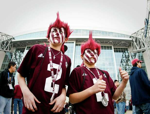 McKane Groover, 11, and his friend Hayden, 11, both of Pearland, wave and show their thumbs as they wait in line to enter Cowboys Stadium to watch Texas A&M play Oklahoma in the Cotton Bowl football game, Friday, Jan. 4, 2013, in Arlington. Photo: Nick De La Torre, Houston Chronicle / © 2013  Houston Chronicle