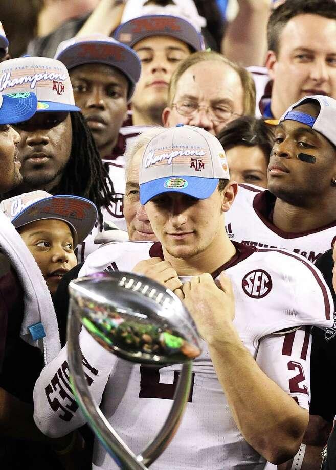 Texas A&M quarterback Johnny Manziel (2) looks into the  Cotton Bowl trophy after beating Oklahoma, Friday, Jan. 4, 2013, in Cowboys Stadium in Arlington. Texas A&M won 41-13. Photo: Nick De La Torre, Houston Chronicle / © 2013  Houston Chronicle