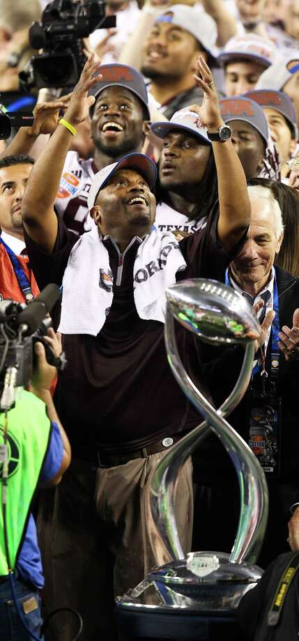 Texas A&M head coach Kevin Sumlin reaches up as confetti falls after being presented with the  Cotton Bowl trophy, Friday, Jan. 4, 2013, in Cowboys Stadium in Arlington. Texas A&M won 41-13. Photo: Nick De La Torre, Houston Chronicle / © 2013  Houston Chronicle