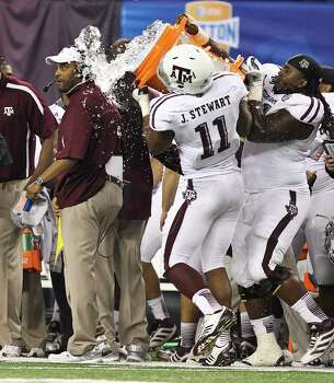 Texas A&M head coach Kevin Sumlin gets dunked with water as his  Cotton Bowl college football game against Oklahoma comes to an end, Friday, Jan. 4, 2013, in Cowboys Stadium in Arlington. Texas A&M won 41-13. Photo: Nick De La Torre, Houston Chronicle / © 2013  Houston Chronicle