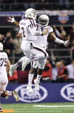 Texas A&M quarterback Johnny Manziel (2) and Texas A&M running back Ben Malena (1) celebrate after scoring a touchdown during the fourth quarter of the Cotton Bowl college football game against Oklahoma, Friday, Jan. 4, 2013, in Cowboys Stadium in Arlington. Texas A&M won 41-13. Photo: Nick De La Torre, Houston Chronicle / © 2013  Houston Chronicle