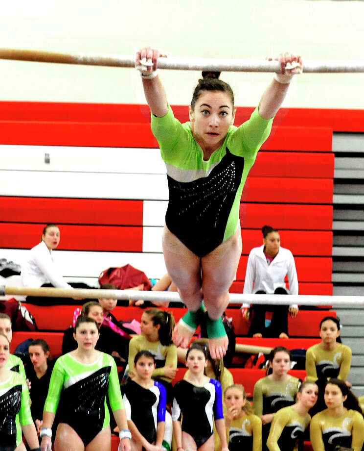 Alison Profeta competes for New Milford High School on uneven parallel bars at the Pomperaug Invitational gymnastics meet in Southbury Saturday, Jan. 5, 2013. Photo: Michael Duffy / The News-Times