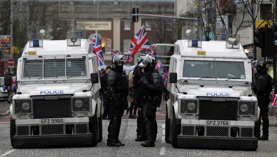 Police in riot gear stand guard as loyalist demonstrators march outside Belfast City Hall in protest over Belfast city council's decision to restrict the number of days the British Union Flag can be flown over the city hall in Belfast, Northern Ireland on January 5, 2013. Nine officers were injured and 18 people arrested in fresh violence overnight on the streets of Belfast, police said. Tensions have risen in the British province since councillors voted on December 3, 2012 to limit the number of days the Union flag can fly over the City Hall to 17, outraging loyalists who believe Northern Ireland should retain strong links to Britain. AFP PHOTO / PETER MUHLYPETER MUHLY/AFP/Getty Images Photo: PETER MUHLY, AFP/Getty Images / AFP
