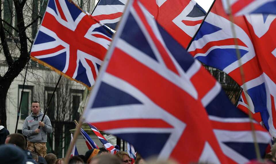 Loyalists flying British Union Flags march outside Belfast City Hall in protest over Belfast city co