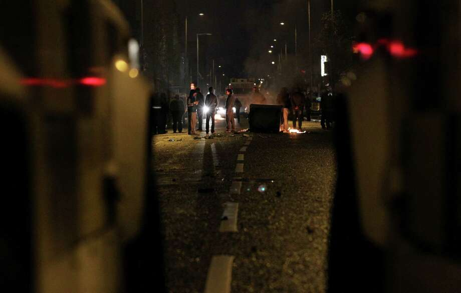 In a picture taken between two police Land Rovers loyalist protesters burn debris on the lower Newtownards road in Belfast, Northern Ireland on January 5, 2013. Nine officers were injured and 18 people arrested in fresh violence overnight on the streets of Belfast, police said on January 5. Tensions have risen in the British province since councillors voted on December 3, 2012 to limit the number of days the Union flag can fly over the City Hall to 17, outraging loyalists who believe Northern Ireland should retain strong links to Britain. AFP PHOTO / PETER MUHLYPETER MUHLY/AFP/Getty Images Photo: PETER MUHLY, AFP/Getty Images / AFP