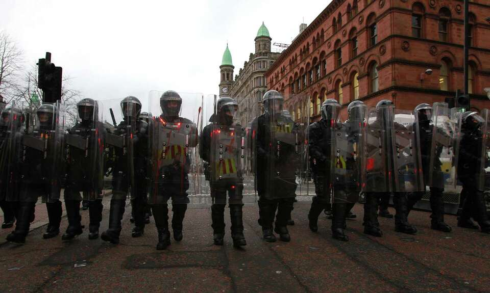 Police in riot gear march behind loyalist protesters after a demonstration outside City Hall in Belf