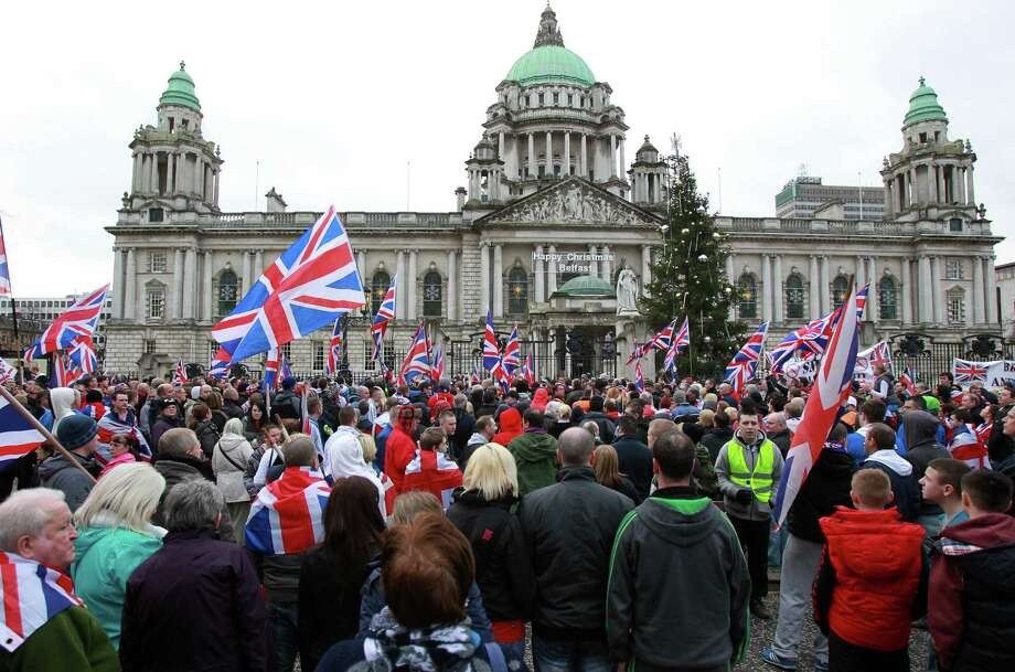 Loyalist march outside Belfast City Hall in protest over Belfast city council's decision to restrict the number of days the British Union Flag can be flown over the city hall in Belfast, Northern Ireland on January 5, 2013. Nine officers were injured and 18 people arrested in fresh violence overnight on the streets of Belfast, police said on January 5. Tensions have risen in the British province since councillors voted on December 3, 2012 to limit the number of days the Union flag can fly over the City Hall to 17, outraging loyalists who believe Northern Ireland should retain strong links to Britain. AFP PHOTO / PETER MUHLYPETER MUHLY/AFP/Getty Images Photo: PETER MUHLY, AFP/Getty Images / AFP