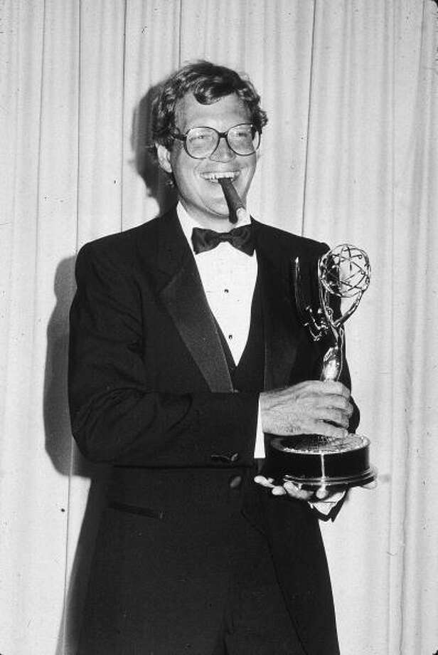 1985: American comedian and talk show host David Letterman smokes a cigar and smiles while holding his trophy for Outstanding Writing - Variety or Music Program at the 37th Annual Emmy Awards. Getty Images