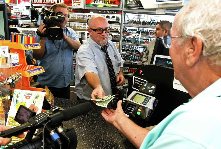 Store manager Bob Chebat, center, hands over Wes Prinzen's modest $4 winnings at a 4 Sons Food Store in Fountain Hills, Ariz., where one of the winning tickets in the $588 million Powerball jackpot was purchased. Photo: Ross D. Franklin, STF / AP