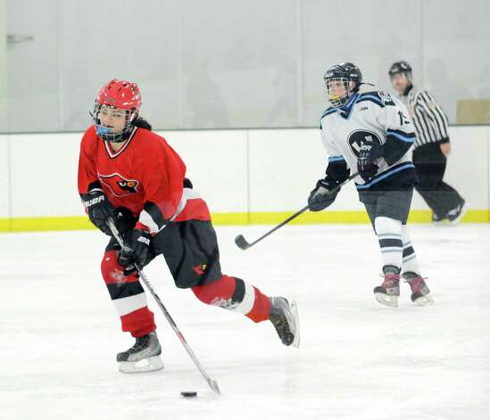 At left, Ciel McDermid of Greenwich advances the puck during the girls high school ice hockey game between Wilton High School and Greenwich High School at the SoNo Ice House in Norwalk, Saturday, Jan. 5, 2013. Greenwich won the game, 4-3. Photo: Bob Luckey / Greenwich Time