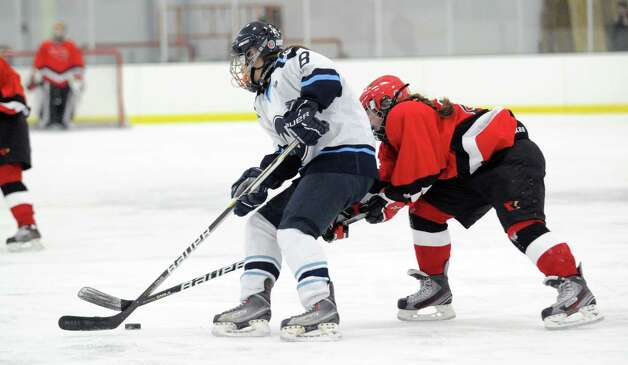 Erin O'Connell, left, of Wilton, attempts to clear the puck while being covered by Erin Ferguson, right, of Greenwich, during the girls high school ice hockey game between Wilton High School and Greenwich High School at the SoNo Ice House in Norwalk, Saturday, Jan. 5, 2013. Greenwich won the game, 4-3. Photo: Bob Luckey / Greenwich Time