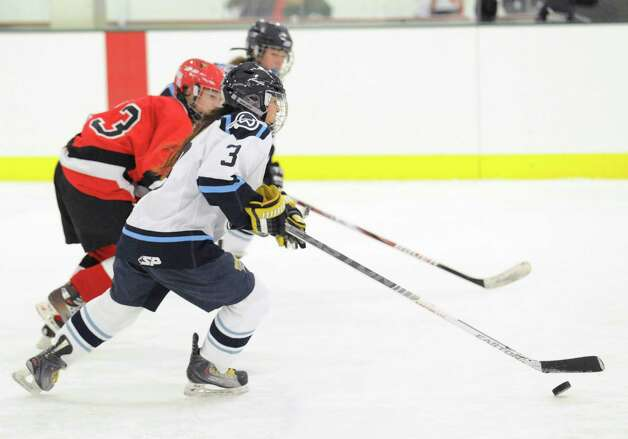 At right, Nicole Lue # 3 of Wilton advances the puck during the girls high school ice hockey game between Wilton High School and Greenwich High School at the SoNo Ice House in Norwalk, Saturday, Jan. 5, 2013. Greenwich won the game, 4-3. Photo: Bob Luckey / Greenwich Time