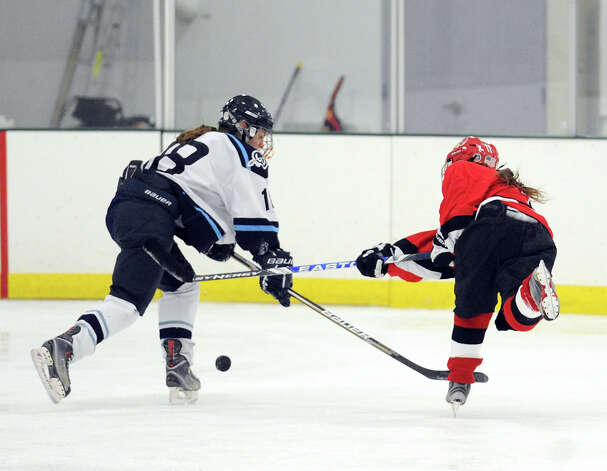 At right, Sara Schectman of Greenwich shoots the puck as Wilton's Erin O'Connell # 18 defends during the girls high school ice hockey game between Wilton High School and Greenwich High School at the SoNo Ice House in Norwalk, Saturday, Jan. 5, 2013. Greenwich won the game, 4-3. Photo: Bob Luckey / Greenwich Time
