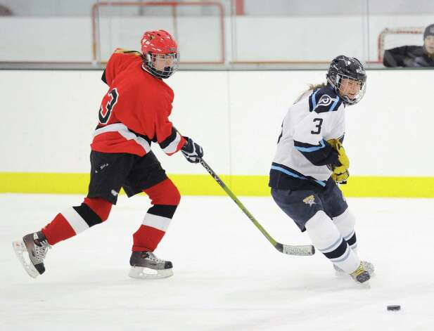 At left, Monique Pera # 3 of Greenwich, shoots the puck past Nicole Lue, also # 3, of Wilton, during the girls high school ice hockey game between Wilton High School and Greenwich High School at the SoNo Ice House in Norwalk, Saturday, Jan. 5, 2013. Greenwich won the game, 4-3. Photo: Bob Luckey / Greenwich Time