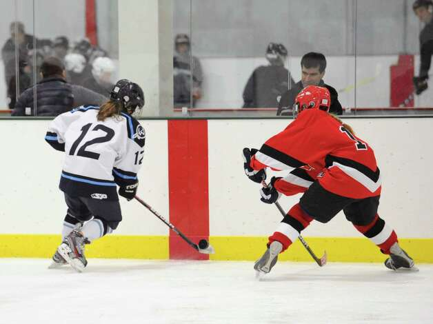 At left, Alex Macarelli # 12 of Wilton goes for the puck against Haley Raftery, right, of Greenwich, during the girls high school ice hockey game between Wilton High School and Greenwich High School at the SoNo Ice House in Norwalk, Saturday, Jan. 5, 2013. Greenwich won the game, 4-3. Photo: Bob Luckey / Greenwich Time