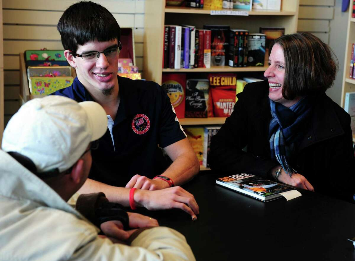 Ryan Boyle, a former Monroe resident and Traumatic Brain Injury survivor, talks with Darren and Kathy Romano, of Monroe, during a book signing for his autobiography