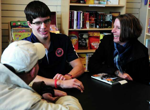 "Ryan Boyle, a former Monroe resident and Traumatic Brain Injury survivor, talks with Darren and Kathy Romano, of Monroe, during a book signing for his autobiography ""When the Lights Go Out""  Saturday, Jan. 5, 2013  at Linda's Story Time in Monroe, Conn. Photo: Autumn Driscoll / Connecticut Post"