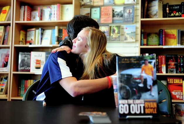 "Ryan Boyle, a former Monroe resident and Traumatic Brain Injury survivor, hugs childhood friend Erica Martino during a book signing for his autobiography ""When the Lights Go Out""  Saturday, Jan. 5, 2013  at Linda's Story Time in Monroe, Conn. Photo: Autumn Driscoll / Connecticut Post"