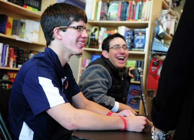 "Ryan Boyle, a former Monroe resident and Traumatic Brain Injury survivor, catches up with Matt Malfettone, 17, during a book signing for his autobiography ""When the Lights Go Out""  Saturday, Jan. 5, 2013  at Linda's Story Time in Monroe, Conn.  Malfettone, a junior at St. Joseph High School who has cerebral palsy, learned a lot from Boyle while he was a student there. Photo: Autumn Driscoll / Connecticut Post"
