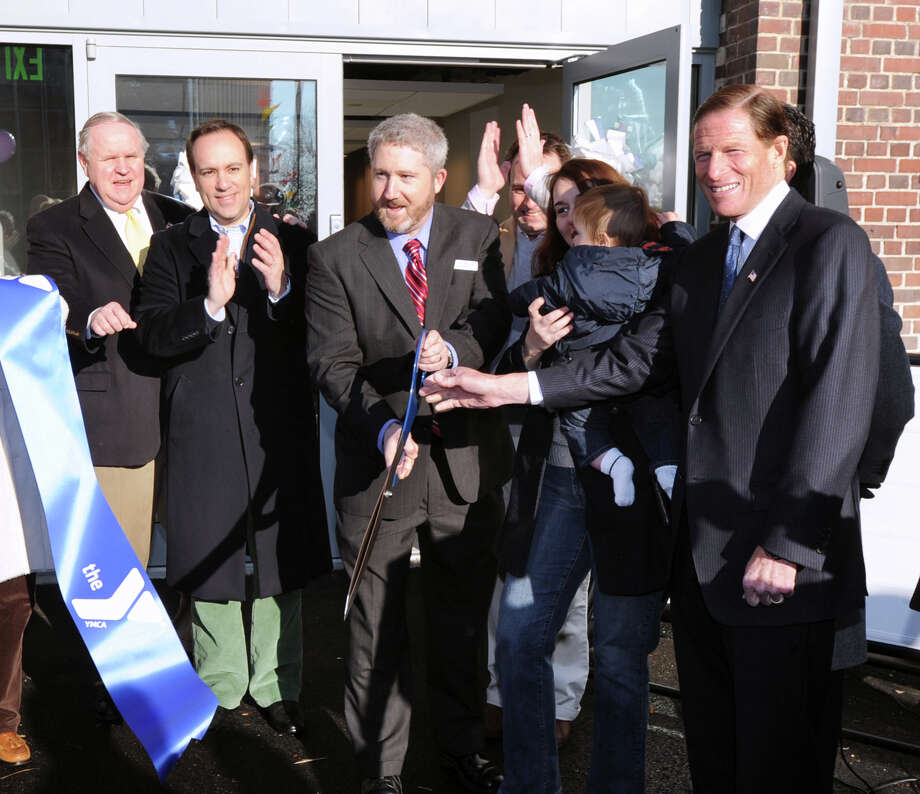 From left, David Theis, selectman, Peter Tesei, first selectman, Ed Philipp, president and CEO of the YMCA of Greenwich, Jen Scarpati holding son, Jesse Schinder, 8 months, and U.S. Sen. Richard Blumenthal, D-Conn., just after Philipp cut the ribbon, with the help of Schinder, the YMCA's youngest member, celebrating the renovations made to the facility , Saturday, Jan. 5, 2013. Photo: Bob Luckey / Greenwich Time