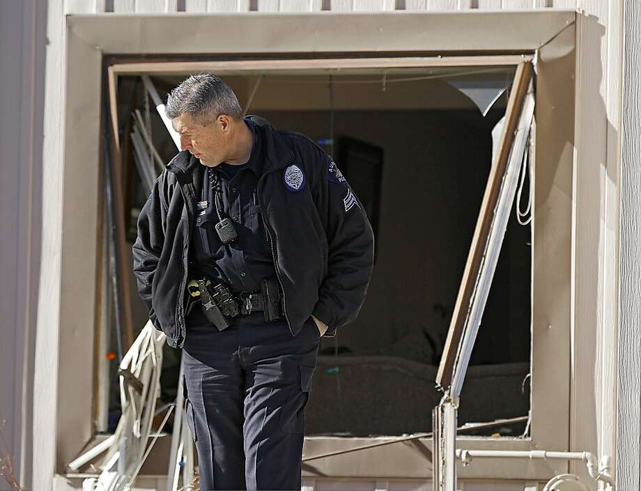 A police officer stands watch at a broken window of an Aurora, Colo., town home. One woman escaped the killing. Photo: Marc Piscotty, Getty Images