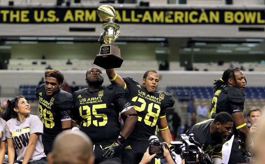 Tray Matthews (28) of Newnan High School in Newnan, Georgia hoists up the championship trophy as teammate Keith Bryant (95) of Atlantic High School in Delray Beach, Florida looks on after the East Team defeated the West, 15-8, in the 2013 U.S. Army All-American Bowl at the Alamodome on Saturday, Jan. 5, 2013. Photo: Kin Man Hui, Express-News / © 2012 San Antonio Express-News