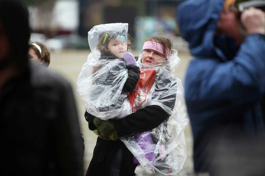 Bon Crowder and daughter Kate Crowder, 3, attempt to stay warm and dry while watching sculptors compete in The Magnificent 7 Ice Carving Competition at Discovery Green on Saturday, Jan. 5, 2013, in Houston. Photo: Mayra Beltran, Houston Chronicle / © 2012 Houston Chronicle