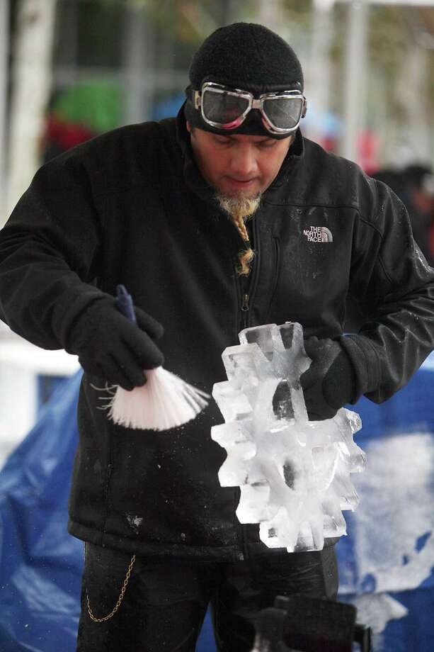 Max Zuleta dusts off excess ice as he quickly works on his sculpture during The Magnificent 7 Ice Carving Competition at Discovery Green on Saturday, Jan. 5, 2013, in Houston. Photo: Mayra Beltran, Houston Chronicle / © 2012 Houston Chronicle