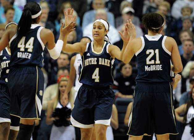 Notre Dame's Skylar Diggins (4) high-fives teammates Ariel Braker (44) and Kayla McBride (21) during the first half of an NCAA college basketball game against Connecticut in Storrs, Conn., Saturday, Jan. 5, 2013. (AP Photo/Jessica Hill) Photo: Jessica Hill, Associated Press / FR125654 AP