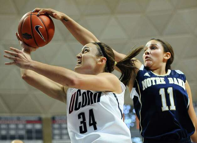 Notre Dame's Natalie Achonwa, right, blocks a shot by Connecticut's Kelly Faris during the first half of an NCAA college basketball game in Storrs, Conn., Saturday, Jan. 5, 2013. (AP Photo/Jessica Hill) Photo: Jessica Hill, Associated Press / FR125654 AP