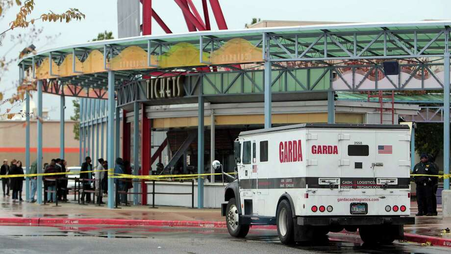 Police investigate the scene of an attempted armored car robbery outside the AMC Studio 30 Theaters Saturday, Jan. 5, 2013, in Houston. One armored car guard was shot and one robbery suspect was shot, the theater remained open after the incident. Photo: James Nielsen, Chronicle / © Houston Chronicle 2012