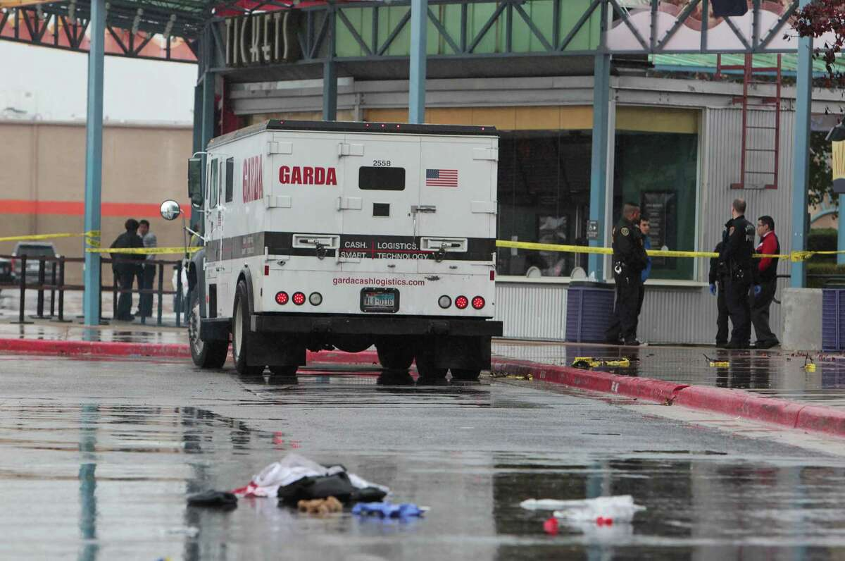 Police investigate the scene of an attempted armored car robbery outside the AMC Studio 30 Theaters Saturday, Jan. 5, 2013, in Houston. One armored car guard was shot and one robbery suspect was shot.