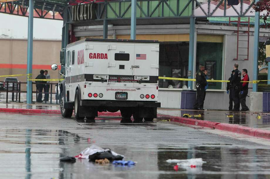 Police investigate the scene of an attempted armored car robbery outside the AMC Studio 30 Theaters Saturday, Jan. 5, 2013, in Houston. One armored car guard was shot and one robbery suspect was shot. Photo: James Nielsen, Chronicle / © Houston Chronicle 2012