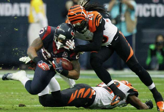 Houston Texans running back Arian Foster (23) is brought down by Cincinnati Bengals free safety Reggie Nelson (20) during the second quarter of an AFC playoff game at Reliant Stadium on Saturday, Jan. 5, 2013, in Houston. Photo: Brett Coomer, Houston Chronicle / © 2013  Houston Chronicle