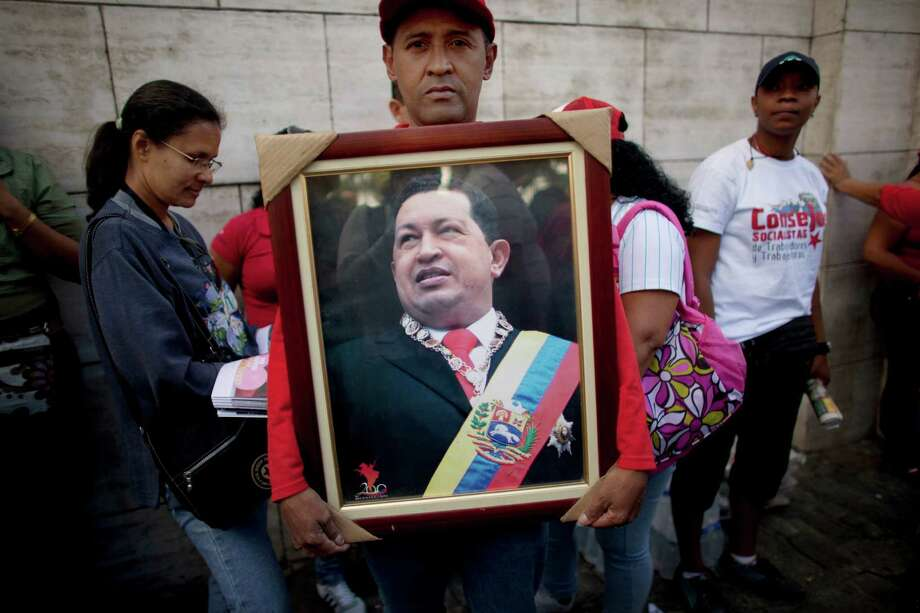 A supporter of Hugo Chavez holds a picture of the ailing Venezuelan president outside the National Assembly in Caracas, Venezuela, on Saturday. Photo: Ariana Cubillos, STF / AP