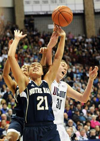 Notre Dame's Kayla McBride (21) and Skylar Diggins, back left, fight for possession of the ball against Connecticut's Breanna Stewart (30) during the second half of an NCAA college basketball game in Storrs, Conn., Saturday, Jan. 5, 2013. McBride and Diggins were top scorers for Notre Dame with 21 and 19 points, respectively.  Notre Dame won 73-72. . (AP Photo/Jessica Hill) Photo: Jessica Hill, Associated Press / FR125654 AP