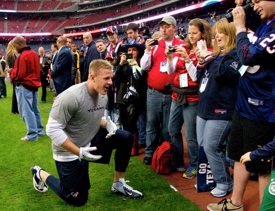 Texans defensive end J.J. Watt takes a knee in front of a group of fans on the sidelines before the game. (Brett Coomer / Chronicle) Photo: Brett Coomer, Houston Chronicle / © 2013  Houston Chronicle