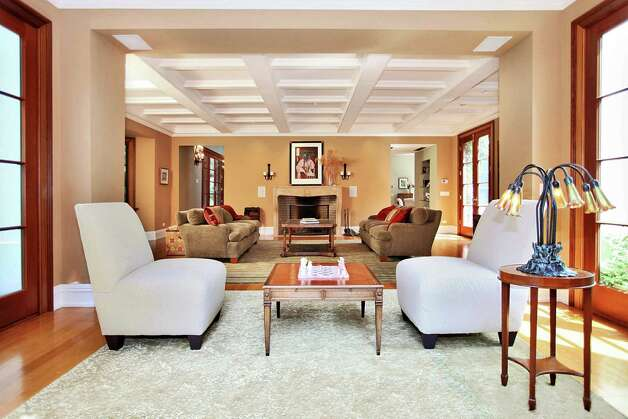 The formal living room features a coffered ceiling and one of the wood-burning fireplaces. A quiet courtyard is off the living room for enjoying the outdoors. Photo: Contributed Photo